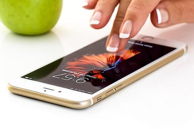 中指でiPhoneを捜査している女性の手