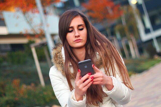 険しい顔でiPhoneを操作している長い髪の女性