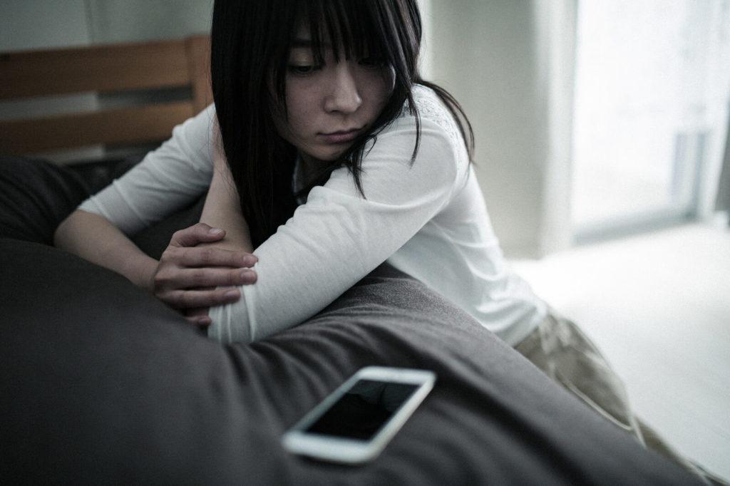 携帯を見つめて座っている女性