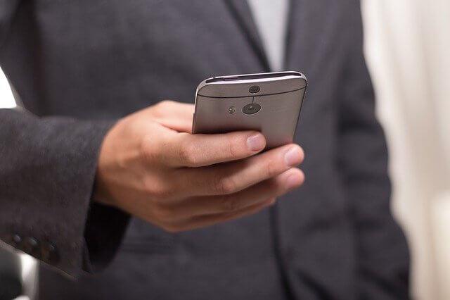 スーツ姿で携帯を触る男性