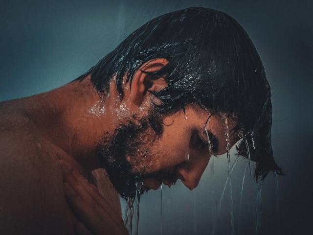 下を向いてシャワーを浴びている髭の生えた男性