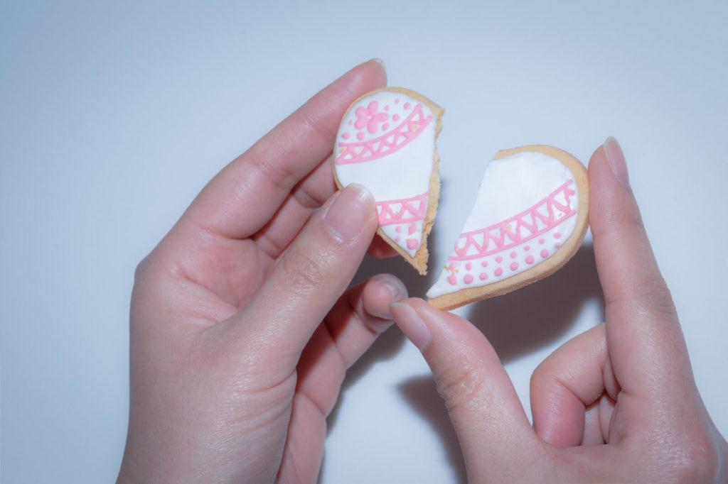 割れているハートのクッキーを持っている手