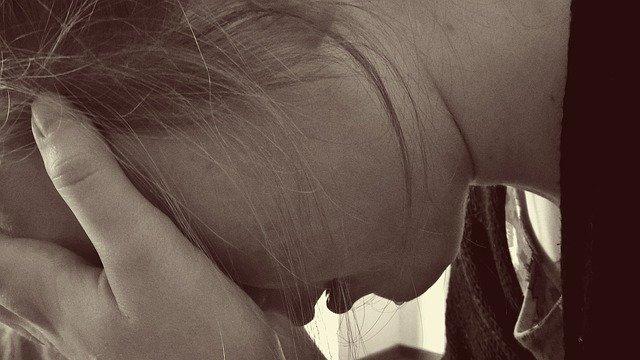 手を多い泣いている横顔の女性