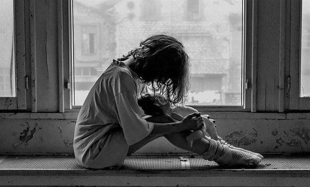 大窓の淵に座り人形を抱いて悲しんでいる女性