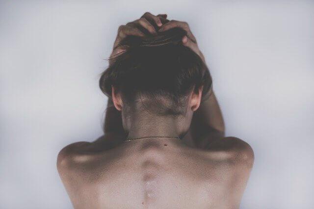 頭を抱える女性の後ろ姿