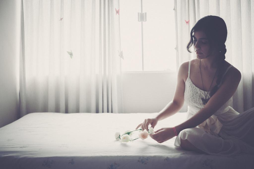 花輪を触りながらうつむいている女性