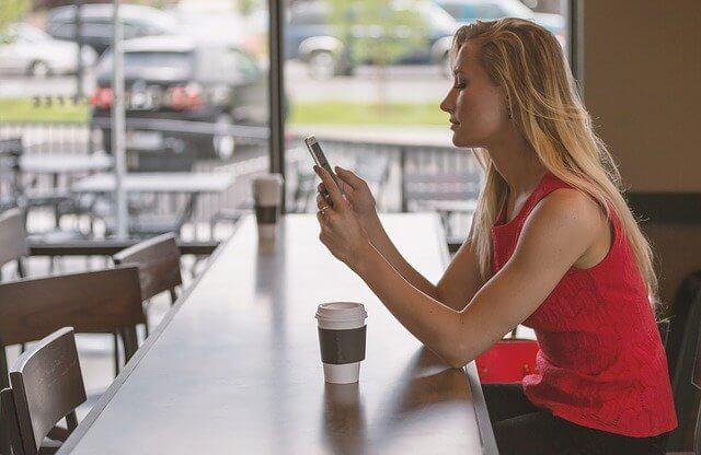カフェで携帯を操作しているブロンドヘアーの女性