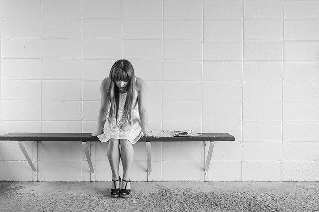 ベンチに座って悲し気な表情をしているワンピース姿の女性