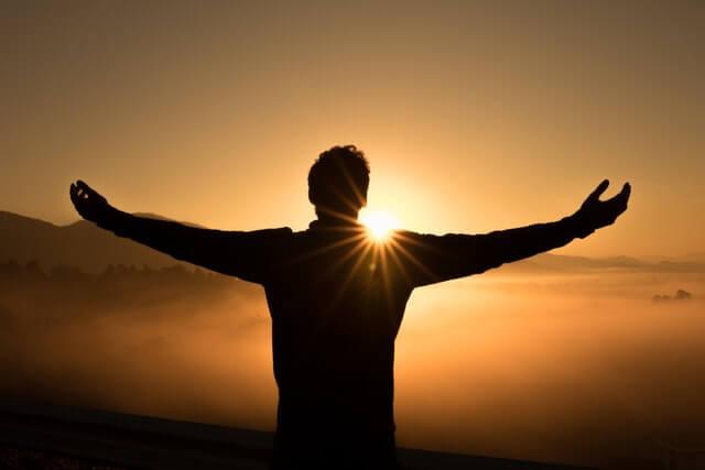 夕陽に手を広げて立つ男性