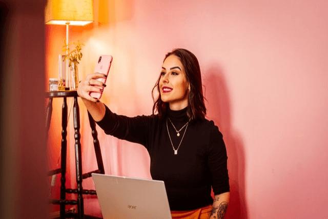 パソコンを開きiPhoneでセルフ写真を撮っている美人な女性
