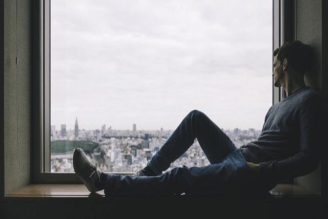 窓枠に座って外を見ている男性
