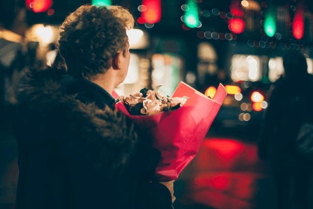 花束を抱える後ろ姿の男性