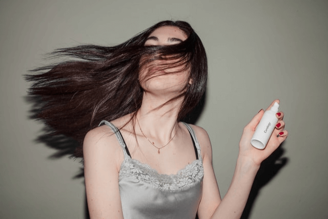 香水を持ち髪を靡かせているキャミソールの女性