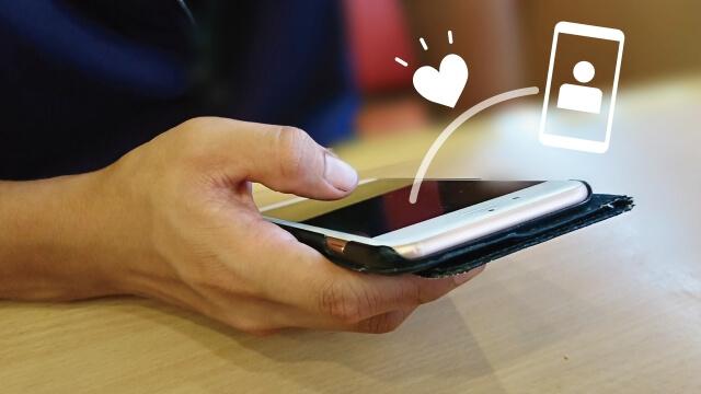 マッチングアプリでメッセージを送信する男性の手