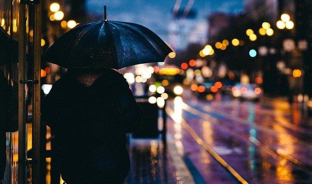 傘をさしながら夜の街を歩く人