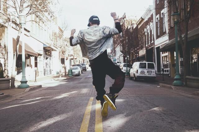 道路の中心で腕を上げてジャンプする帽子をつけた男性