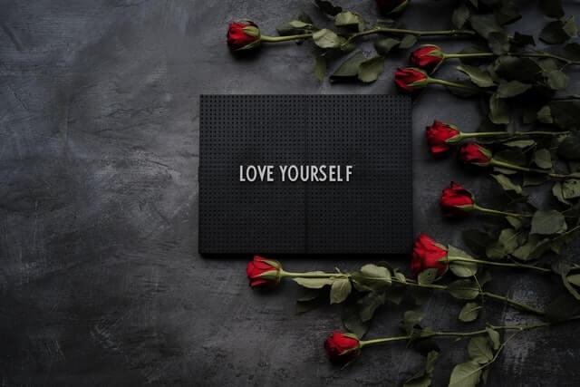 黒いボードに描かれたLOVE YOURSELFと並んでいる赤いバラ