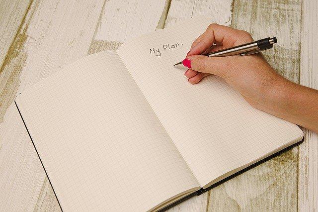 ノートに予定を書いている女性の手
