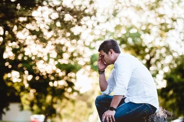 木の椅子に座り片手で頭を抱えている白シャツの男性