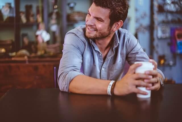 コーヒーを持ってカフェで休む男性