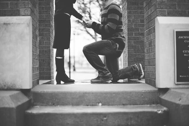 女性の手を取り膝をつく男性