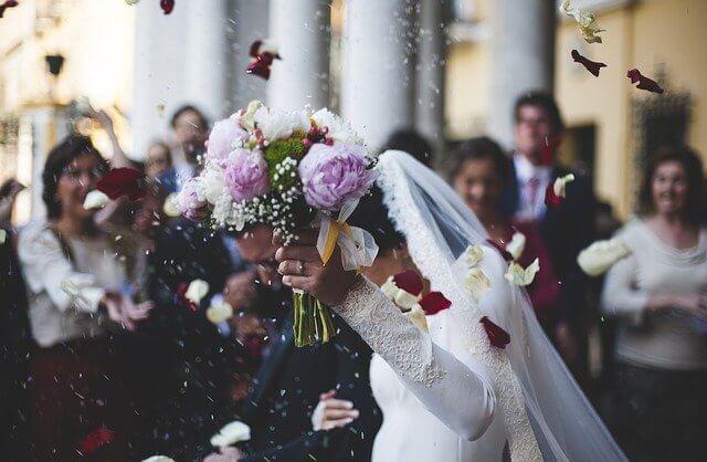 結婚式でブーケを持ち手を上げる新婦