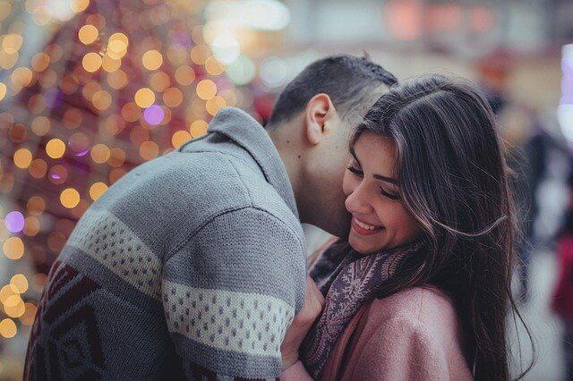 外で女性の頬にキスをしている男性
