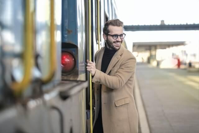 メガネと茶色いコートを着て電車に乗る男性
