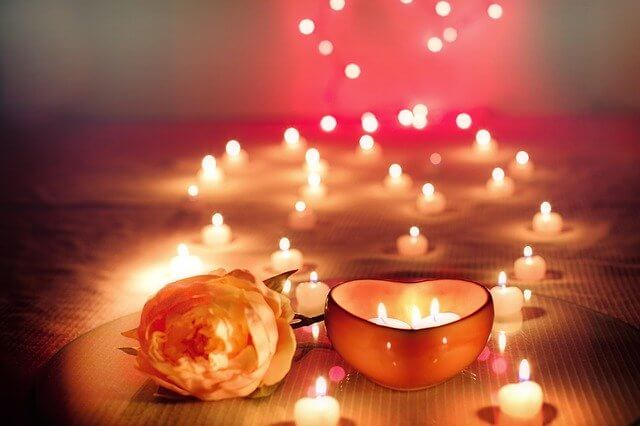 火が灯されているハートのアロマキャンドルとバラ