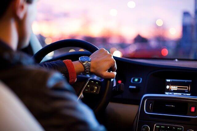 運転している高級時計をつけた男性