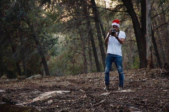 クリスマスの帽子をかぶって森林で写真を撮る一人の男性