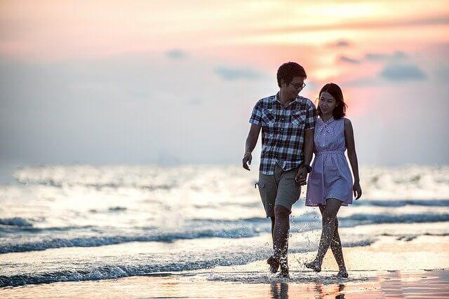 海辺で手を繋いで歩く男女