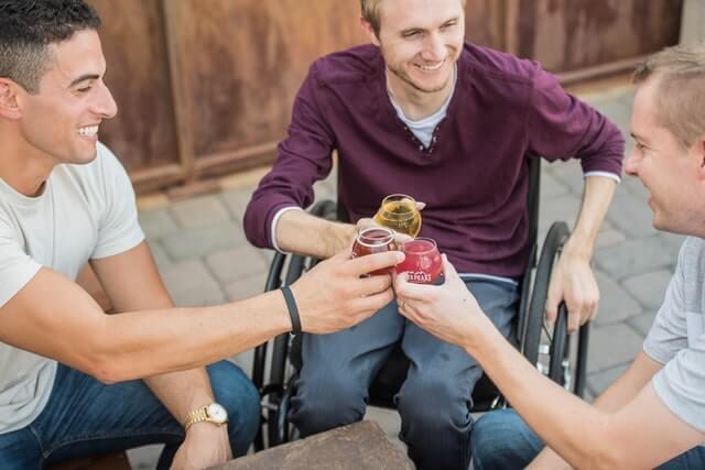 車いすの男性1人とベンチに座る男性2人が笑顔で乾杯