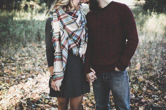 遊歩道で手を繋ぎ、顔を寄せ合うカップル