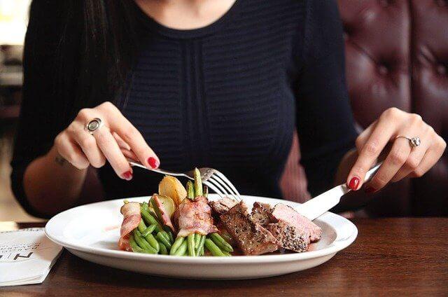 ステーキをナイフとフォークで食べる女性