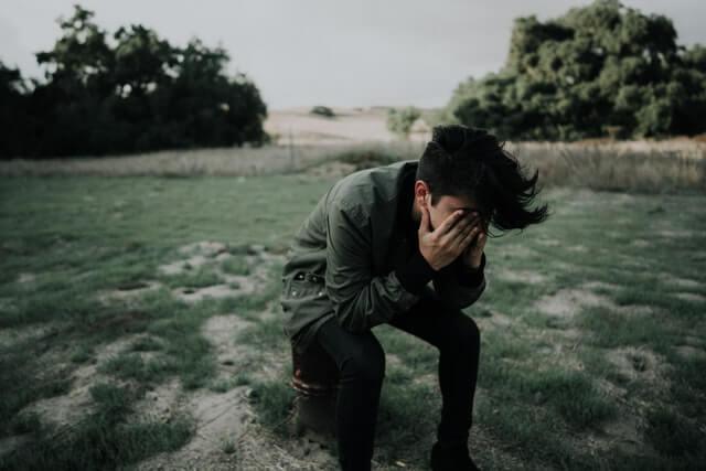 芝生の土地で目を隠しうつむく男性
