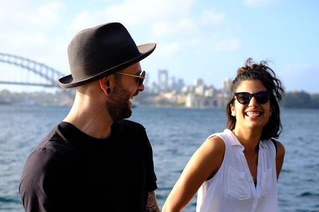 湾岸で話すサングラスをかけた笑顔の男女