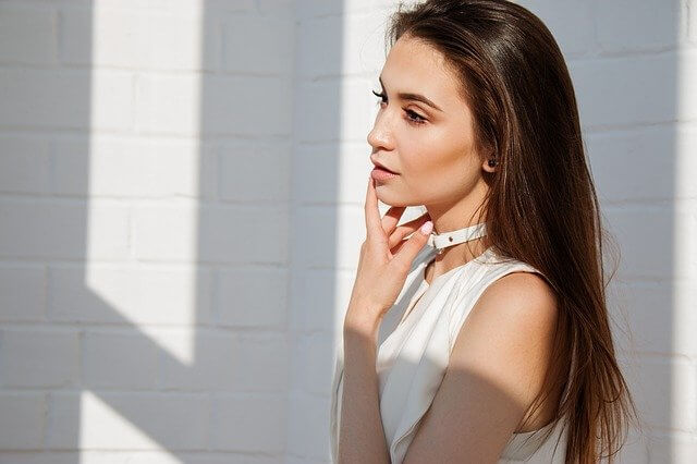 手を顎と首に沿えているロングヘア―の女性