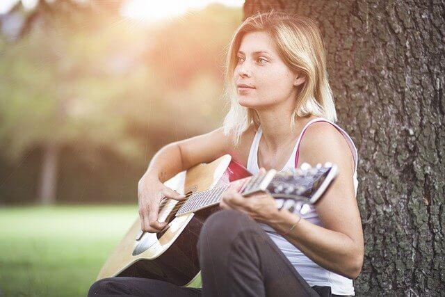木を背もたれにしてギターを弾く女性