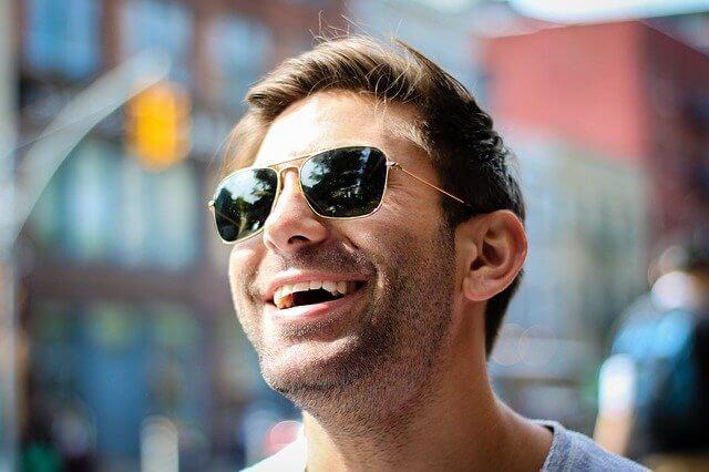 サングラスをかけて笑顔で上を向く男性