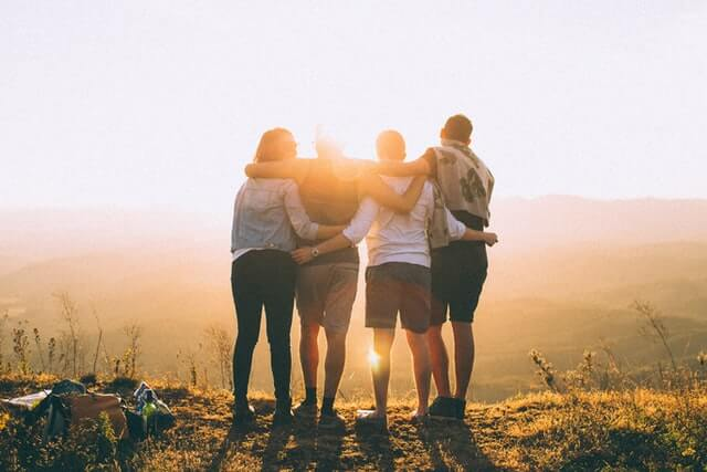 夕陽を見ながら肩を組む4人の男女