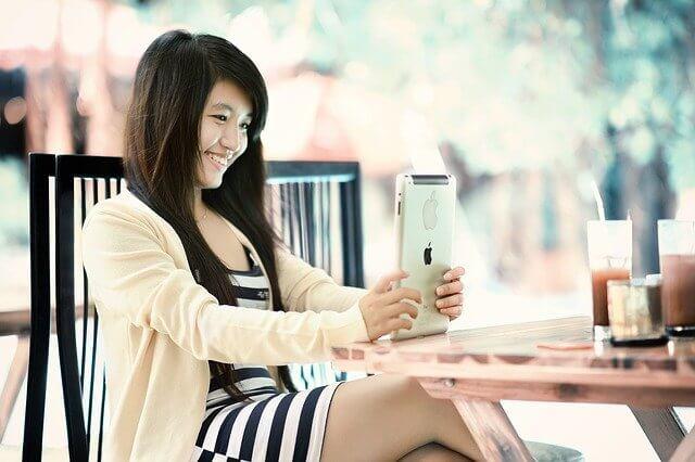 カフェでipadを触る笑顔の女性