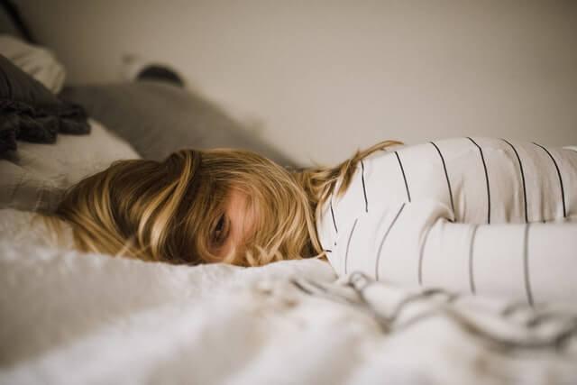 ベッドにうつ伏せで寝転ぶブロンドヘアーの女性