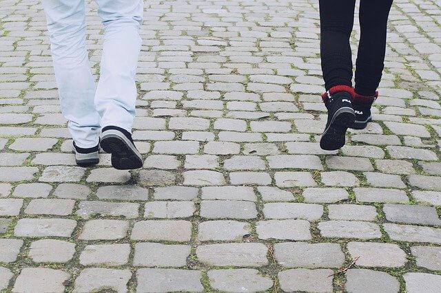 白いレンガの道を歩く男女の足