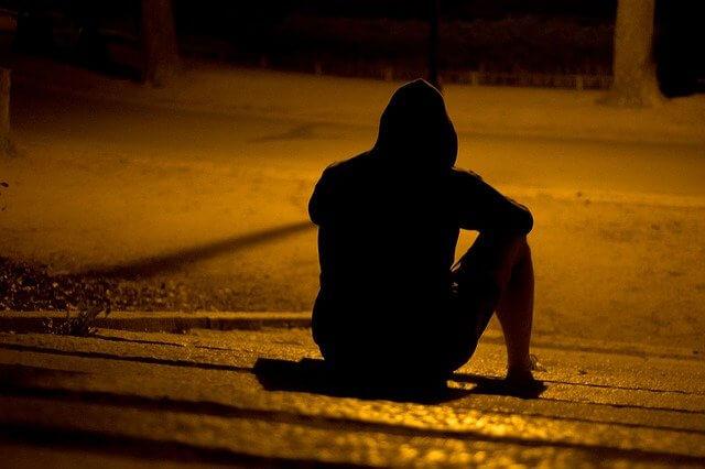 夜の公園で座る一人ぼっちの男性