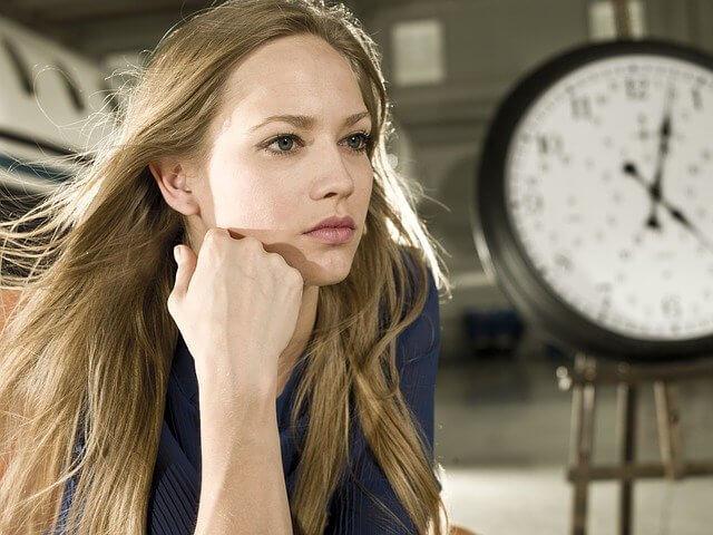 時計塔の下に座る手を顎に添えた女性
