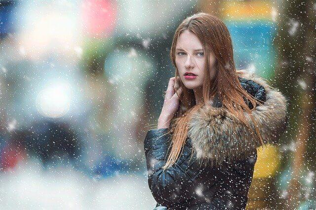 吹雪の中で神妙な顔で前を向く女性