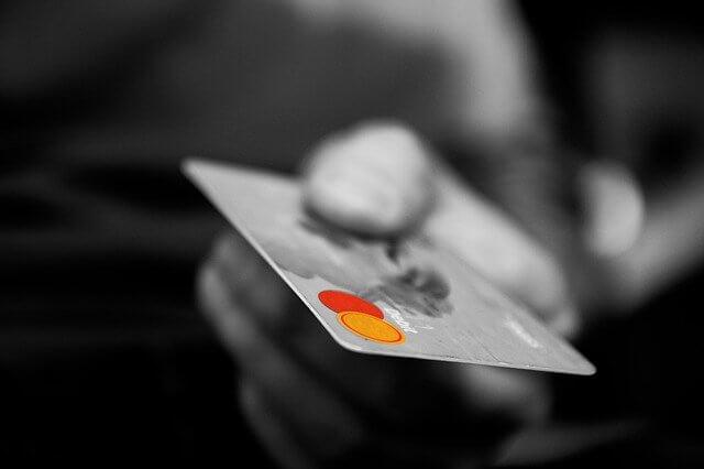 クレジットカードを差し出す男性の手