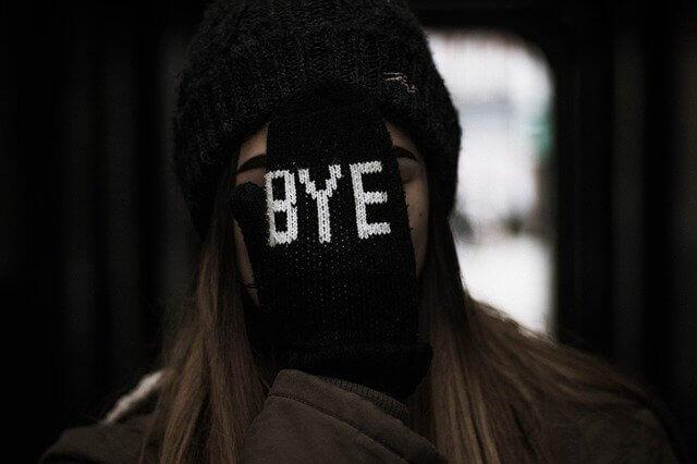 さよならと書いた手袋を顔にあてる女性