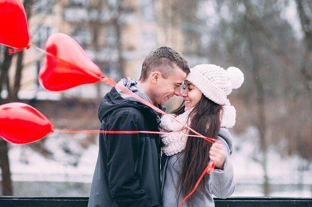 顔を近づける男性とハートの風船を持つ女性